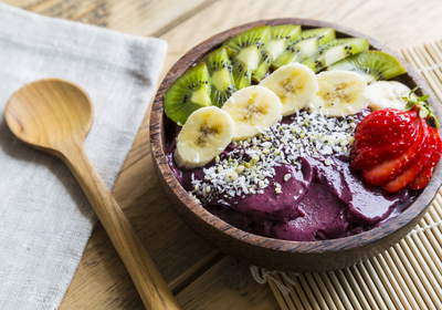 Acai Bowl topped with banana, hemp seeds, kiwi fruit and a strawberry