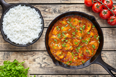 Image of tandoori chicken dish with white rice, parsley and tomatoes