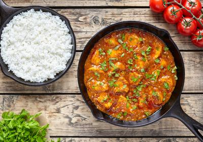 Image of tandoori chicken dish with white rice, parsley and tomatoes